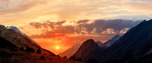 Panorama of a mountain valley in summer, aerial view. Fairytale sunset over the mountain peaks, amazing nature, summer in the mountains. Travel, tourism. beautiful background picture of nature