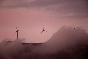 Wind turbines operate atop a mountain during sunset near the town of Kalavrita