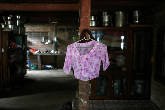 A blouse belonging to Kyu Kyu Win, who says she is going through a divorce with an abusive husband, hangs on a shelf at a house in Dawei