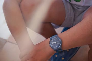 Wrist watch close up teenager sitting on skateboard