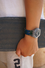 Grey masculine watch on young boy's hand holding skateboard