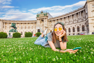 Young asian woman using her smartphone for internet surfing lying on a green grass in Vienna Wall mural
