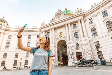 Young asian tourist taking selfie photo on her smartphone in Vienna, Austria