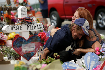 Antonio Basco, whose wife Margie Reckard was murdered during a shooting at a Walmart store, is comforted by a woman next to a white wooden cross bearing the name of his late wife, at a memorial for the victims of the shooting in