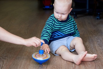 Mom shows her son how to play with a spinning top. Cute boy in a striped sweater plays with whirligig on the floor.