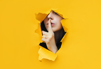 Obraz A young girl closes her lips with her index finger,making it clear to the viewer that you need to observe silence,keep a secret and not say too much. Censorship and harassment of freedom of speech. - fototapety do salonu