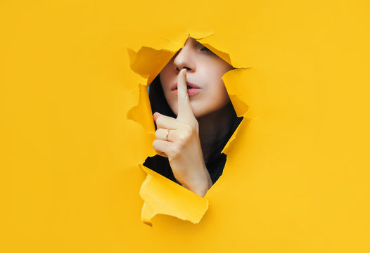 A young girl closes her lips with her index finger,making it clear to the viewer that you need to observe silence,keep a secret and not say too much. Censorship and harassment of freedom of speech.