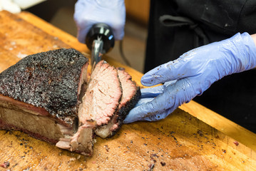 Barbecued and smoked brisket being cut and served on wooden board