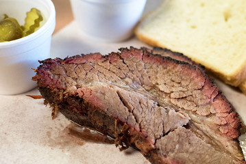 Slices of barbecue brisket served with bread and pickles, a classic southern USA offering