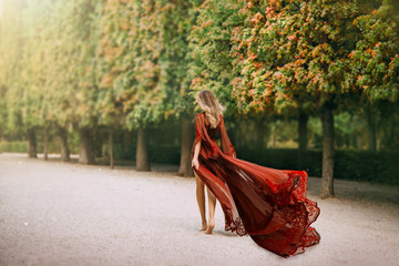 Mysterious blond woman in a red evening dress, walks in the autumn park barefoot. The wind blows a long train and hair. Queen in her garden. Rear view, shooting from the back without a face