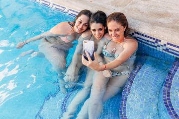 Group of beautiful young girlfriends sitting by the pool taking a photo with mobile phone. Outdoor shot. Friendship concept