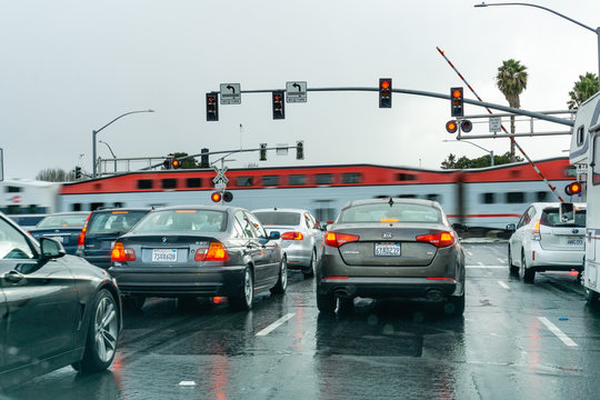 February 2, 2019 Sunnyvale / CA / USA - Vehicles waiting at a red traffic light; high speed train passing in the background, San Francisco bay area, California