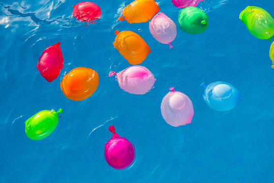 Group of many colorful plastic water balloons floating in the water of a pool to entertain their children on summer vacations.