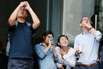 People watch and take photos of French urban climber Alain Robert climbing the Cheung Kong Center building in Hong Kong