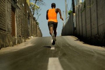 Back view of athletic black African American professional sport man running training hard outdoors on asphalt road during jogging workout in healthy lifestyle