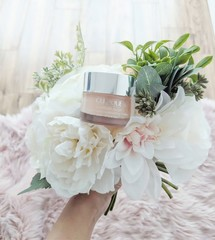 Clinique skincare product held in hand with flowers