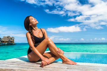 Wall Mural - Luxury Bora Bora vacation hotel woman sunbathing relaxing at overwater bungalow suite in Tahiti resort, French Polynesia travel destination.