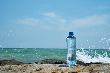 Plastic bottle. Coast of the sea. Waves hit the stones.