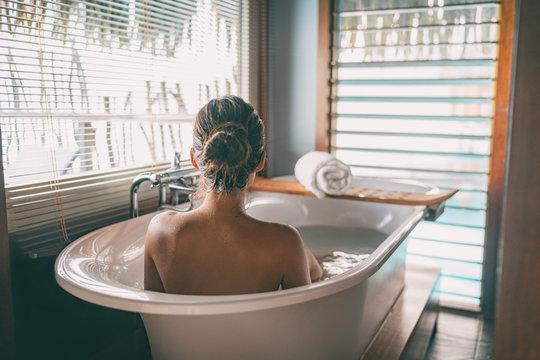 Luxury bath woman wellness spa relaxing soaking in warm water bathtub of hotel suite.