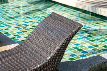 Rattan chaise lounge near swimming pool in tropical hotel, closeup