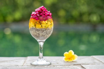 Chia seeds pudding with red dragon fruit, passion fruit, mango and avocado in a glass for breakfast on the background of the swimming pool water, closeup. The concept of healthy eating.