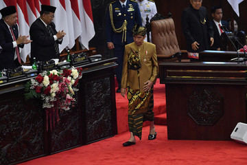 Indonesia President Joko Widodo walks after delivering a speech in front of the parliament members ahead of Independence Day, at the parliament building in Jakarta