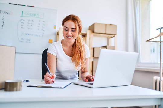 Young female business owner sitting in office writing sales and deliveries on paper sheets while using laptop