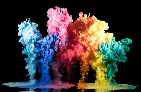 Colorful rainbow paint drops from above mixing in water. Ink swirling underwater