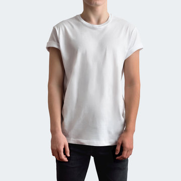Young slim man in a blank T-shirt and black jeans on a white studio background.