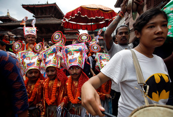 Boys dressed as holy cows participate in a parade to mark Gaijatra Festival in Kathmandu