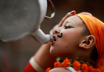 A boy is offered milk as he participates in a parade to mark Gaijatra festival in Kathmandu