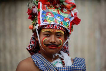 A boy dressed as holy cow participates in a parade to mark Gaijatra Festival in Kathmandu