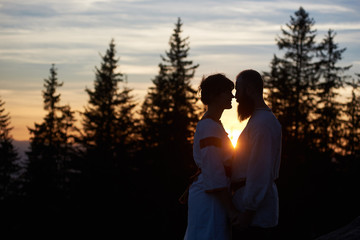 Silhouettes of young couple in love in the evening. Bearded man and happy woman touching noses, smiling and looking at each other's words. Beautiful sunset, cloudy sky and forest on blurred background