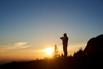 Silhouette of young male photographer with photo camera standing beside tourist tent on the top of mountain in the morning at sunrise. On background beautiful view of rising sun and blue sky.