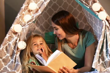 Happy woman with her little daughter reading book in hovel at home Wall mural