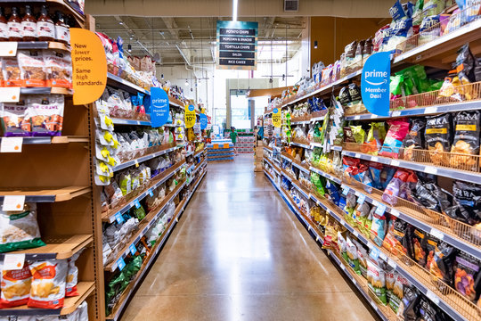 June 21, 2019 Los Altos / CA / USA - View of an aisle in a Whole Foods store, Amazon Prime Member offers visible on the shelves; south San Francisco bay area