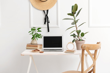 Stylish workplace with modern laptop near white wall