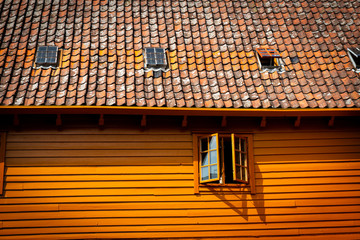 Fragment of traditional wooden house with tile roof and window.