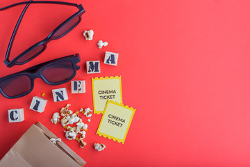 craft bag with popcorn 3d cinema glasses tickets wooden cubes with text on red background creative flatlay