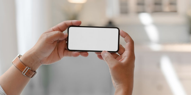 Close-up view of man holding horizontal blank screen smartphone
