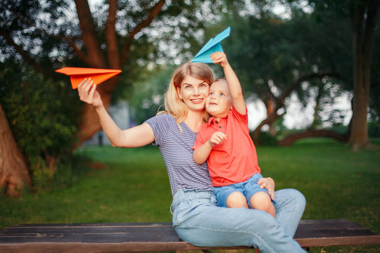 Young blonde Caucasian mother and boy toddler son sitting together on wooden bench outdoor on summer sunset and playing with colored paper airplanes. Happy family childhood lifestyle.