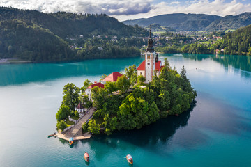 Bled, Slovenia - Beautiful morning at Lake Bled (Blejsko Jezero) with the Pilgrimage Church of the Assumption of Maria and traditional Pletna boats on the water on a bright summer day