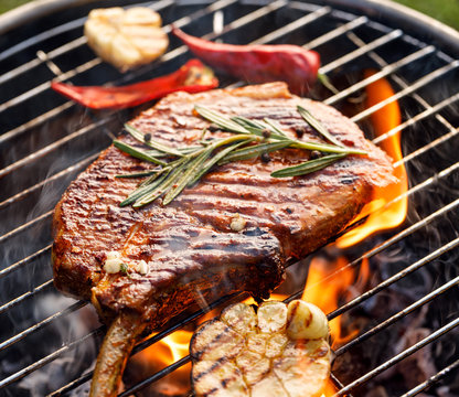 Grilled bone-in pork chop, pork steak, tomahawk in spicy marinade on e a grill plate, close-up. Barbecue, bbq meat