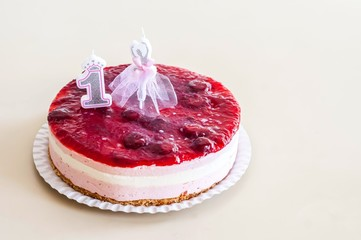 Sweet white and pink mousse cake with several layers and strawberry jam topping with a 1 year old birthday candle and a ballet dancer candle. One year old birthday party celebration concept image.