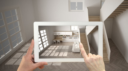 Augmented reality concept. Hand holding tablet with AR application used to simulate furniture and design products in empty interior with parquet floor, modern white kitchen, top view Wall mural