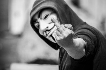 Paris - France - 19 May 2018 - portrait of man with Vendetta mask  making bad gesture with hand. This mask is a well-known symbol for the online hacktivist group Anonymous