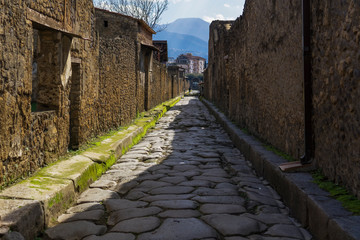 Pompeii, Italy secondary narrow street along remaining houses. Day view of structured formation of cobblestoned path to accommodate traffic inside the town.
