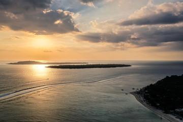 Dramatic sunset over the 3 Gili island, Air, Meno and Trawangan, in Lombok, Indonesia.