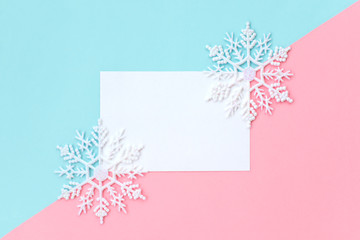 White paper card decorated with snowflakes on pink and light blue background. New Year, Christmas and winter concept. Flat lay, top view, free copy space. Wall mural