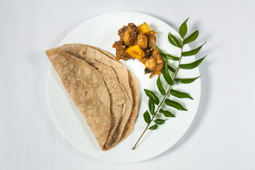 Top view of a plate of Indian Chapati and Chicken curry with curry leaves as garnish